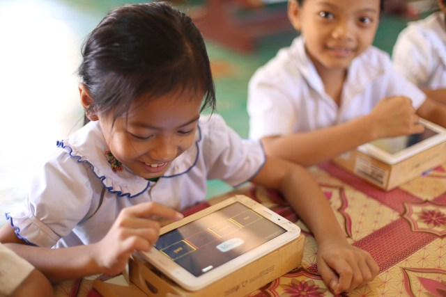A girls plays a reading game on a tablet in a classroom in Cambodia.