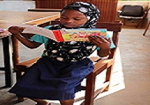 Seven year-old Maifa learning how to read in Mozambique