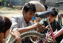 Aung Than works with Wide Horizons students in a community development project repairing bicycles for local students.