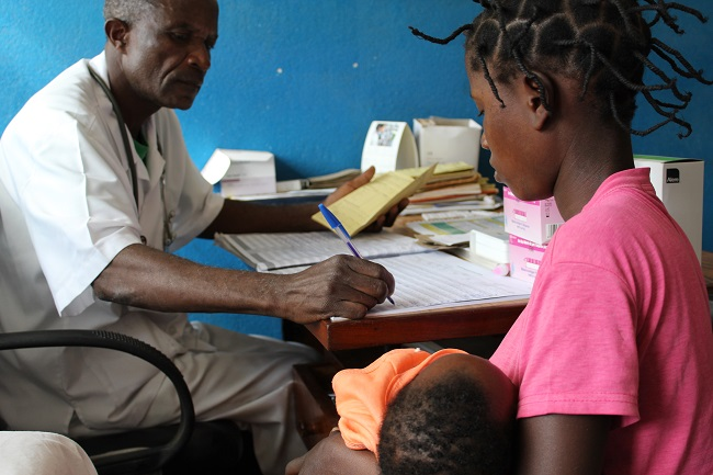 During the sick child consultation, Zacarias Morruela, the health technician, fills in a new child health registration book.